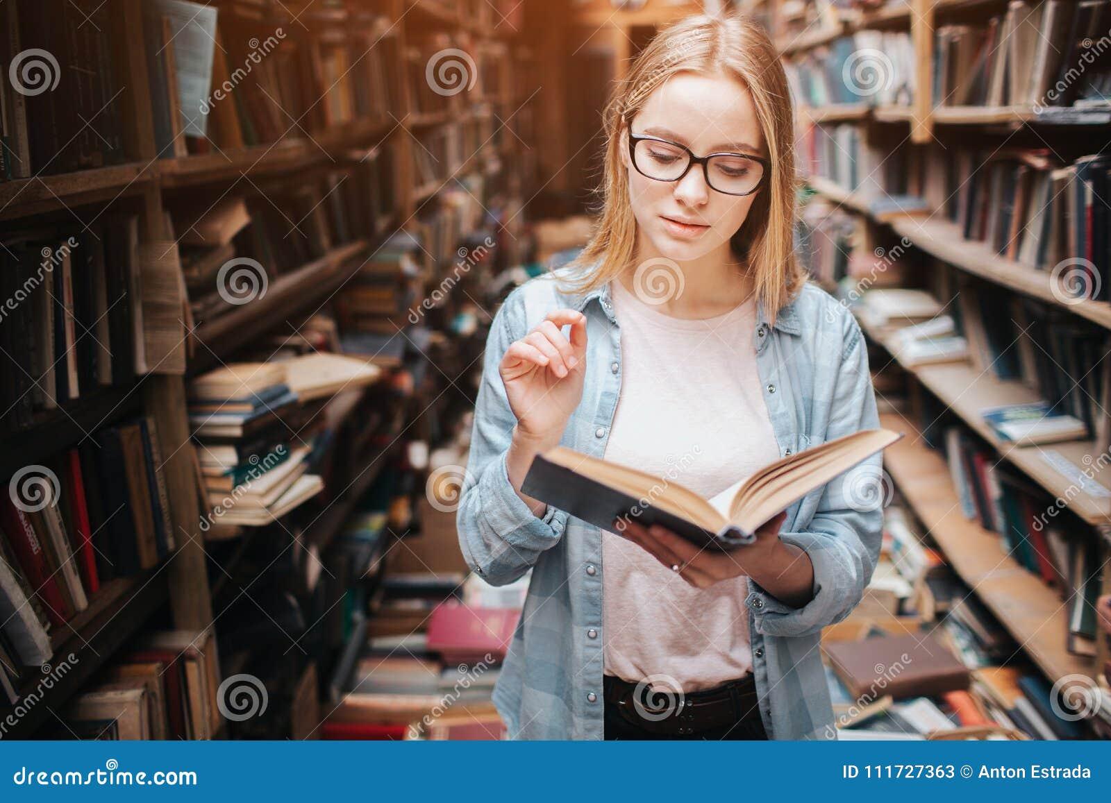 年轻少年在公立图书馆 她找到一本书并且读了它 这个女孩是镇静平安和体贴的