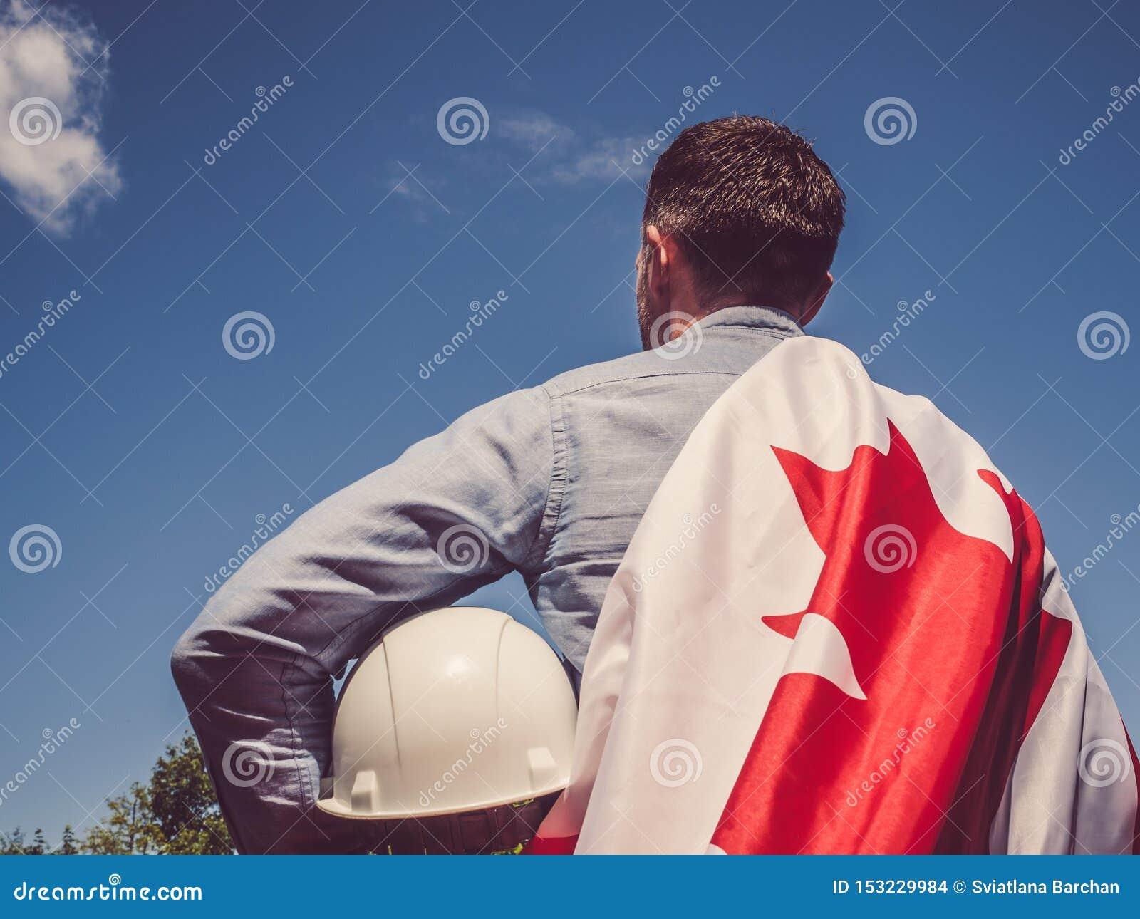 年轻工程师、白色安全帽和加拿大旗子