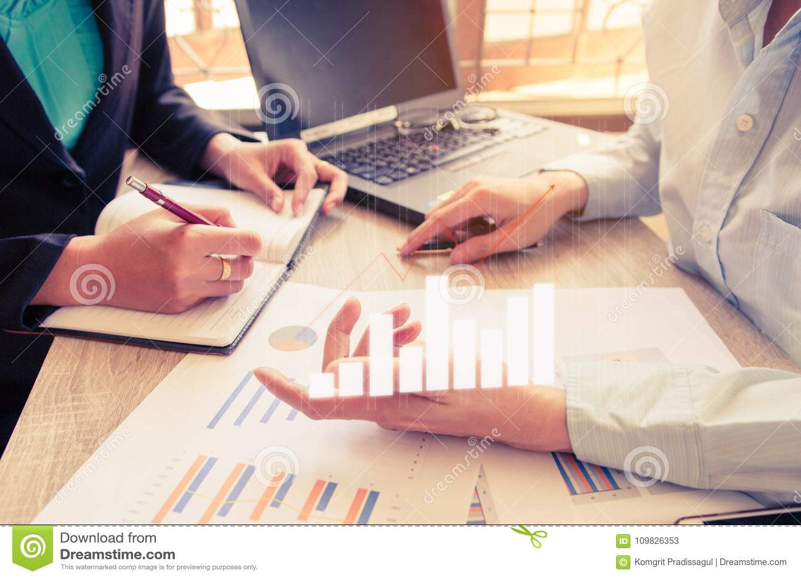 年轻帐户经理乘员组工作和谈论计划财政图表数据在办公室