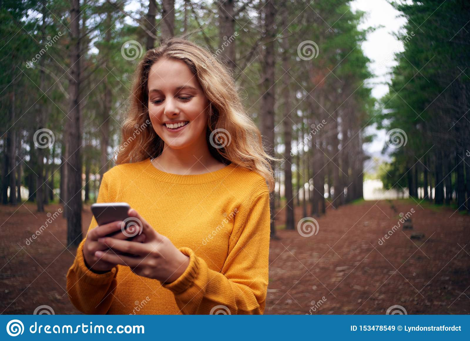 年轻微笑的妇女在使用手机的森林里