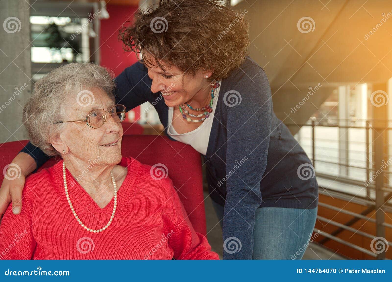 年轻微笑的妇女拥抱的资深妇女