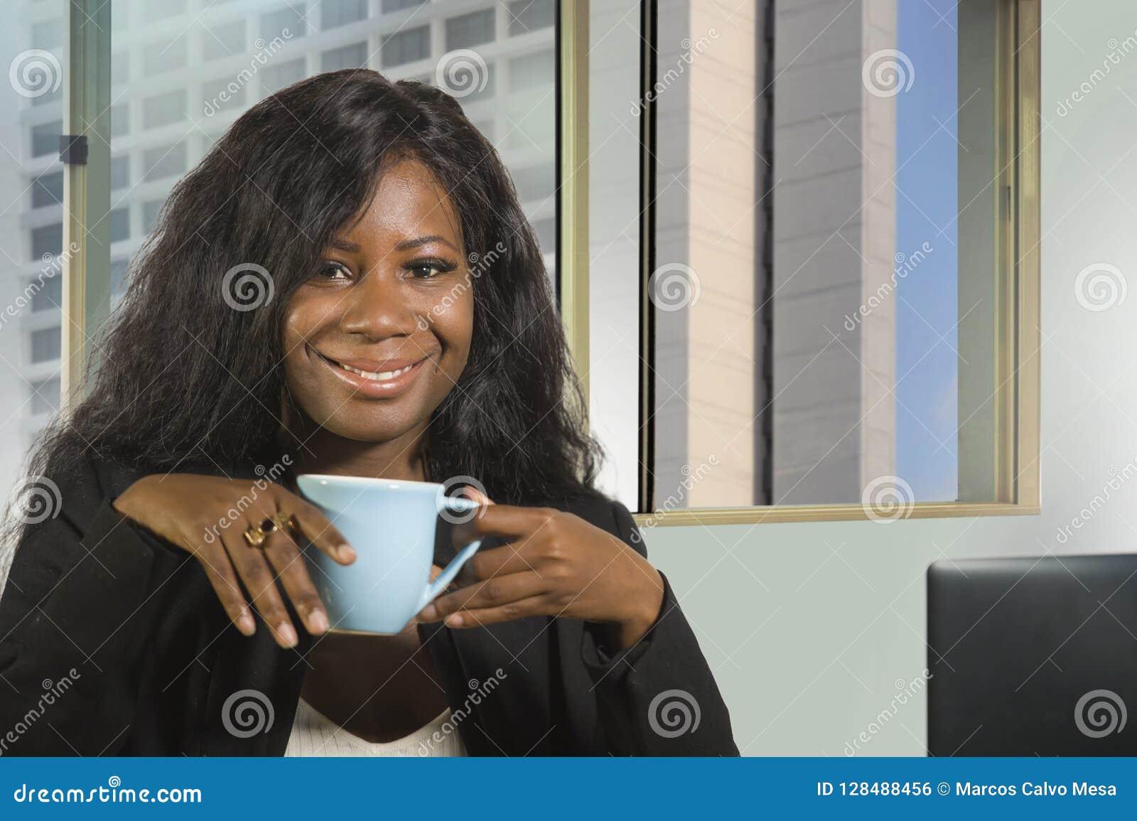 年轻愉快和有吸引力黑非裔美国人女实业家工作确信在计算机书桌饮用的咖啡微笑的satisfi