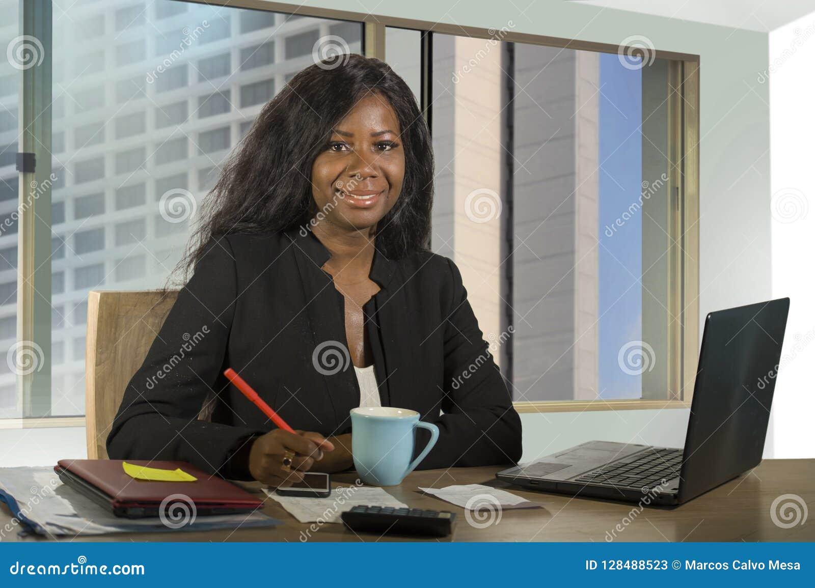 年轻愉快和有吸引力黑非裔美国人女实业家工作确信在计算机在财政满意的书桌微笑