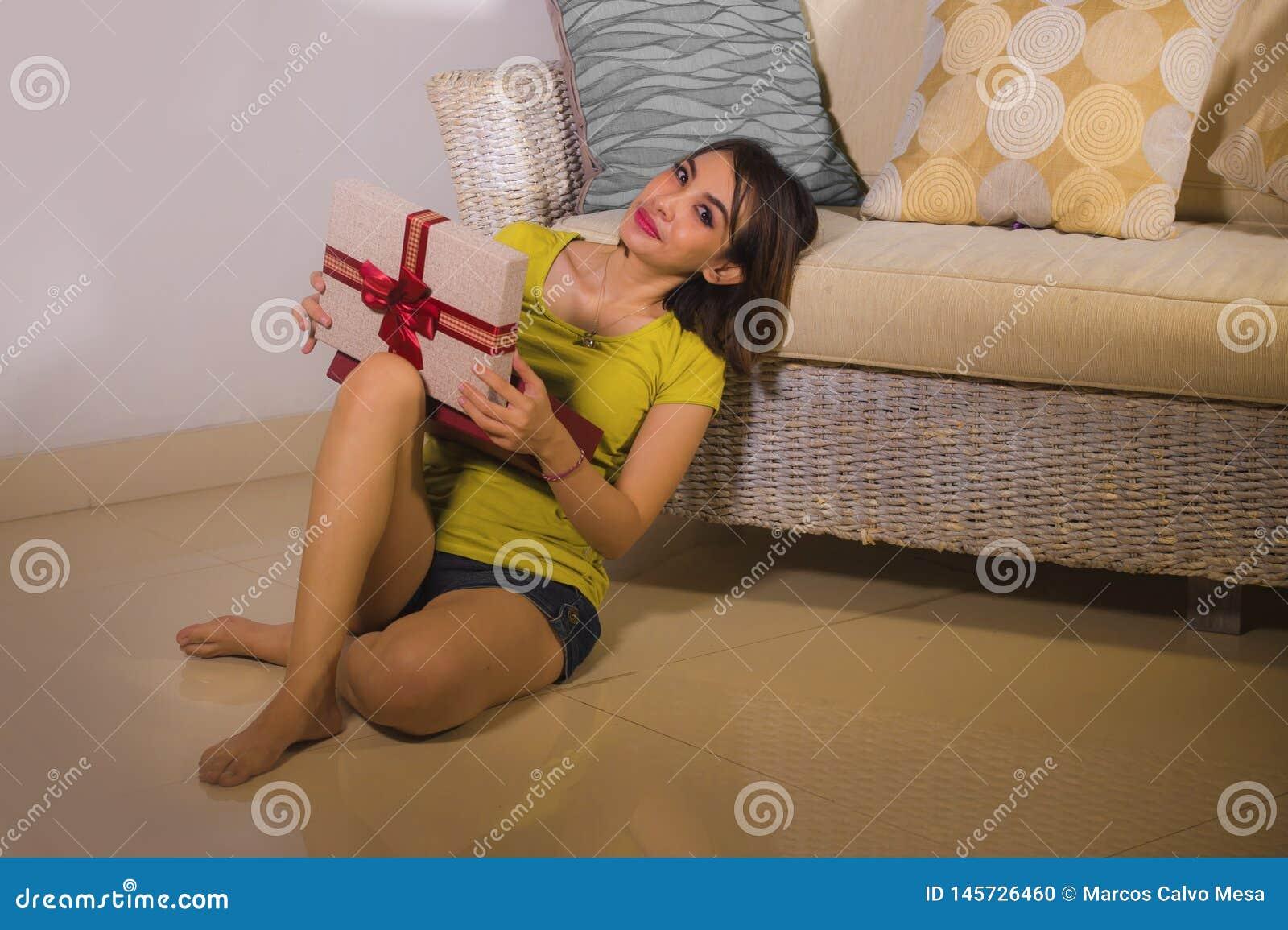 年轻愉快和美丽的亚裔印度尼西亚妇女打开的圣诞节或生日礼物箱子生活方式画象有红色丝带的
