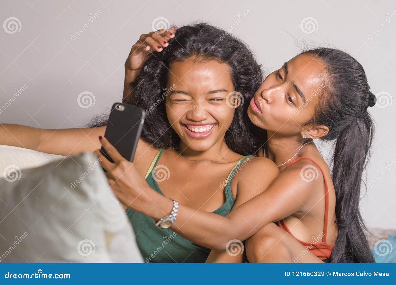 年轻愉快和美丽的亚裔姐妹或女朋友在家结合与手机的微笑的快乐的采取的selfie照片