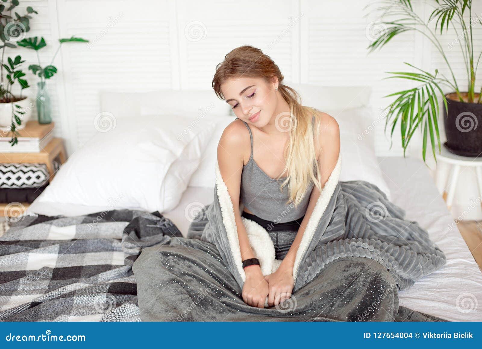 年轻愉快的妇女坐在温暖的大气的白色毯子早晨包裹的床
