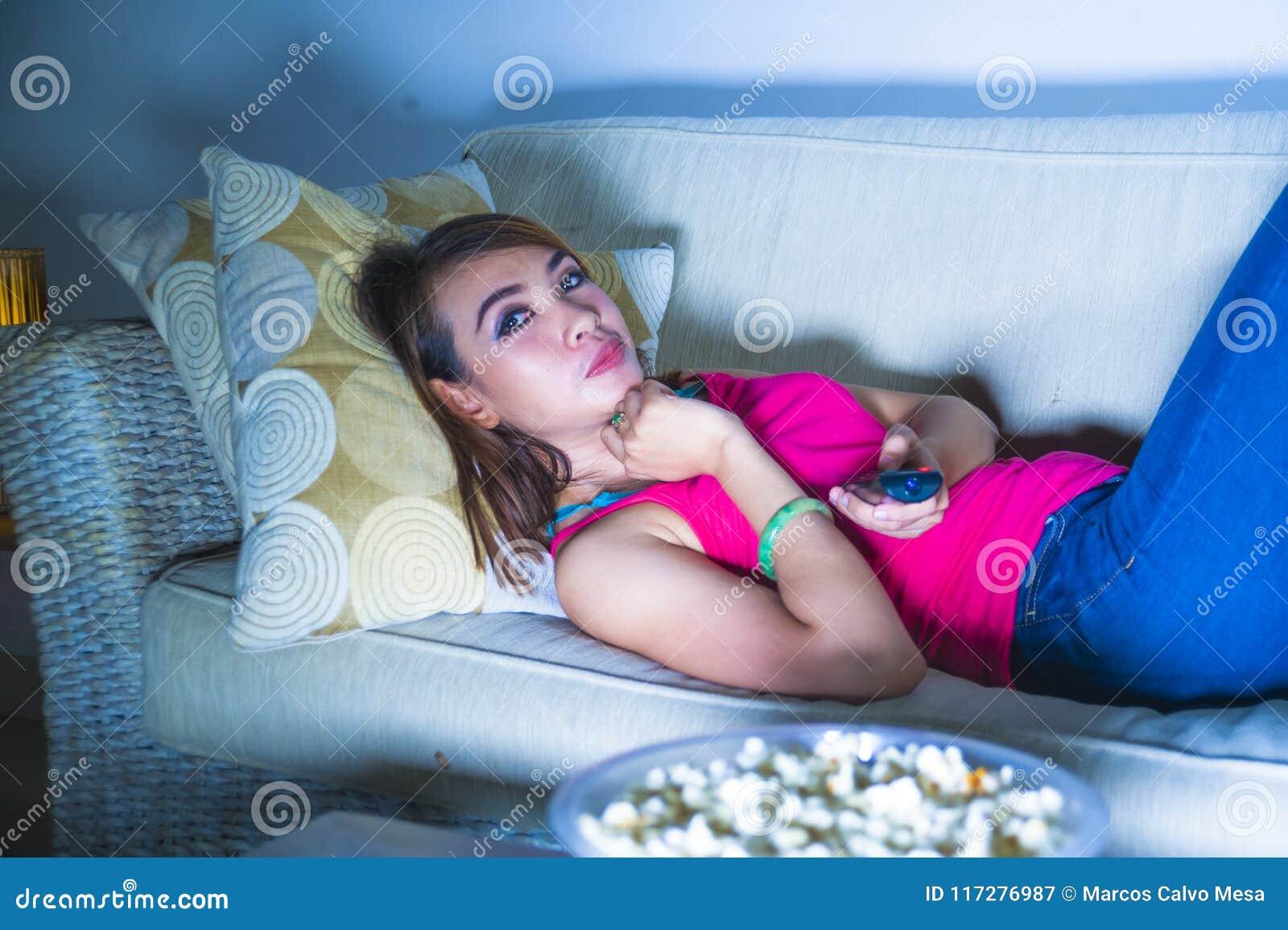 年轻愉快的西班牙拉丁吃玉米花的妇女沙发长沙发观看的电视在享受单独电视喜剧m的晚上在家放松了