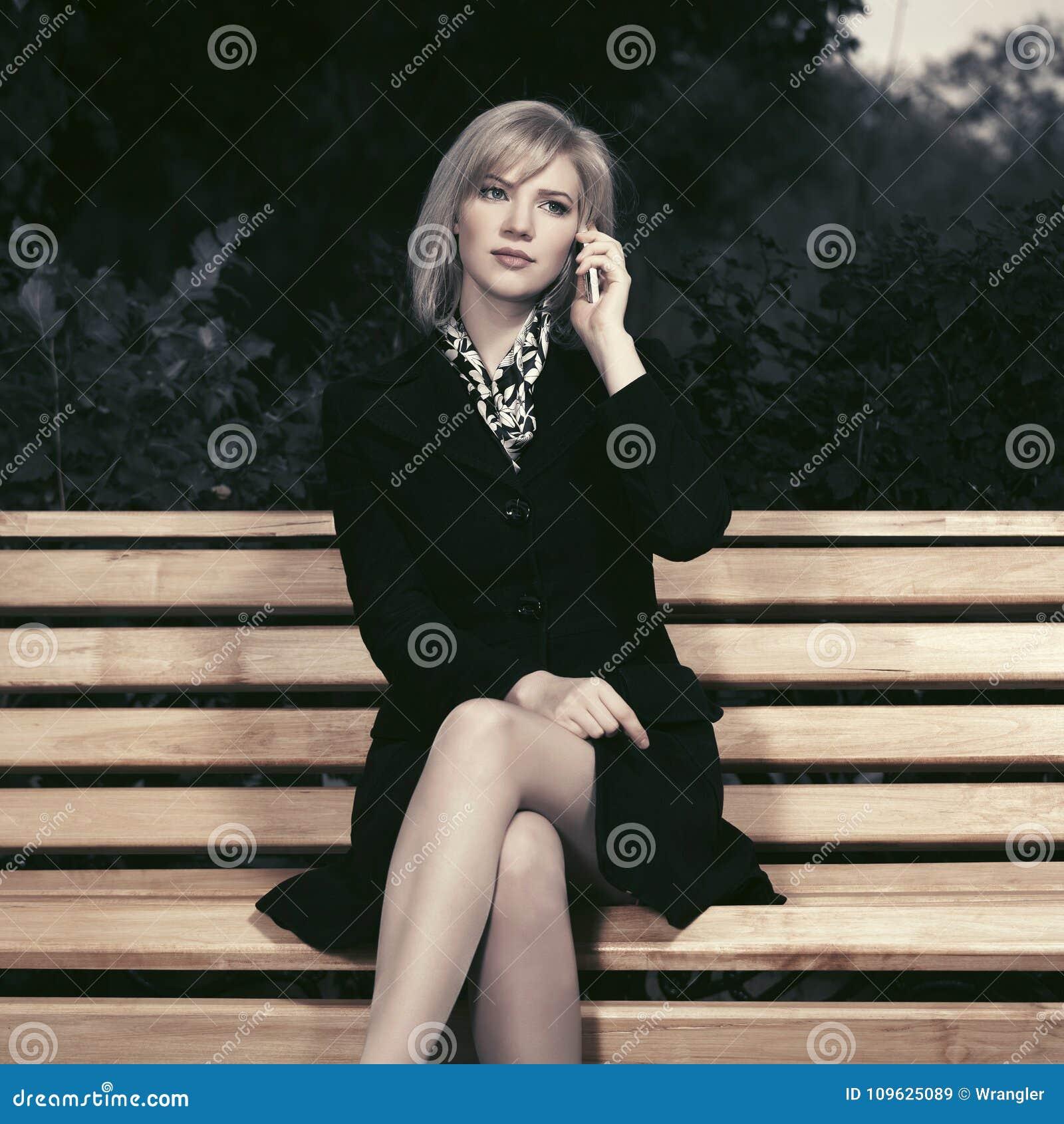 年轻时尚白肤金发的妇女谈话在手机坐长凳