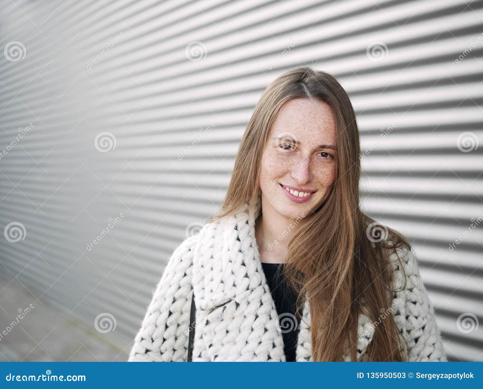 年轻时髦穿戴的严肃白种人妇女摆在室外在都市城市被弄脏的几何背景冷天