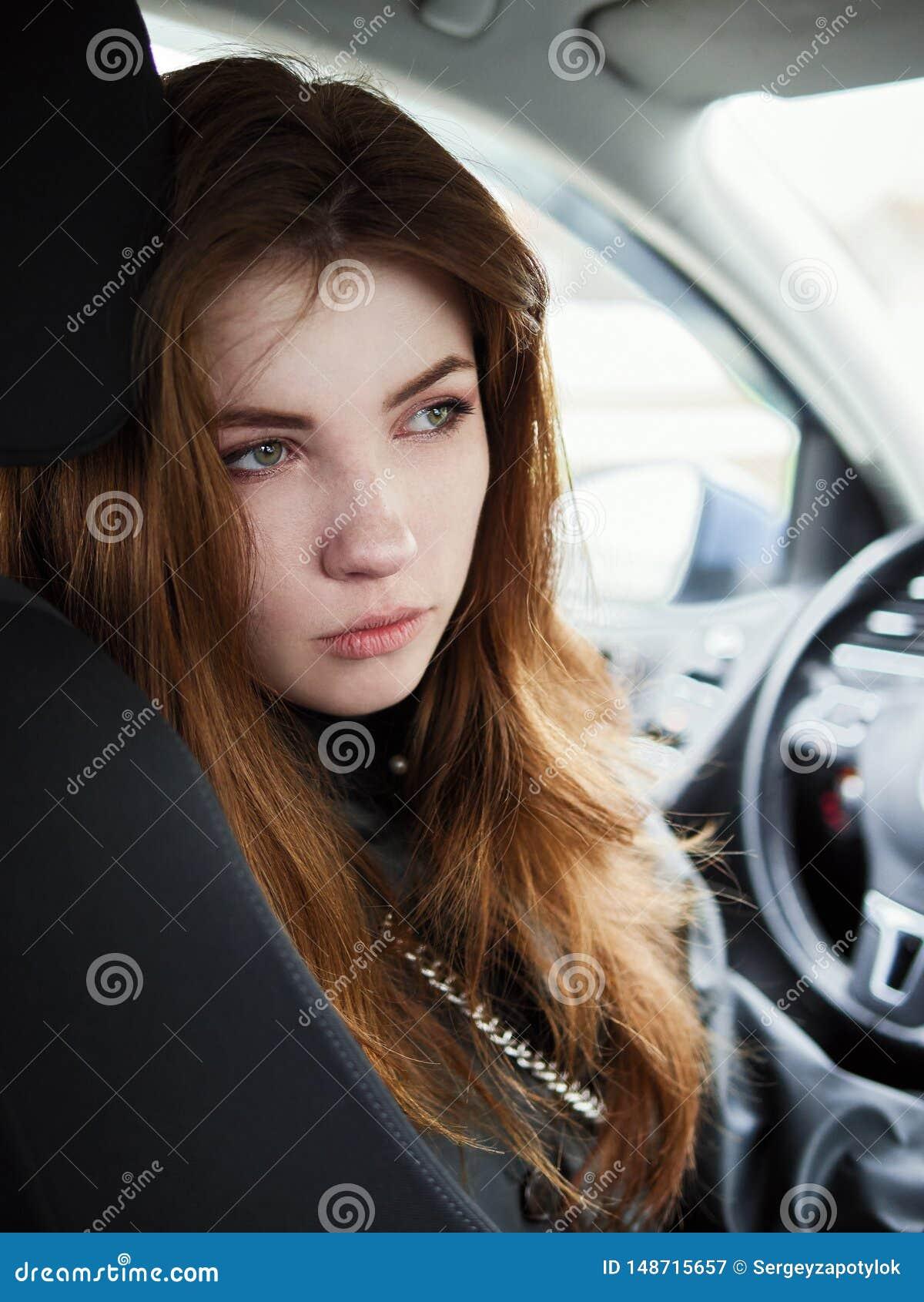 年轻有吸引力的红色回顾从驾驶席的头发自己经营的女商人司机接近的画象困住在a