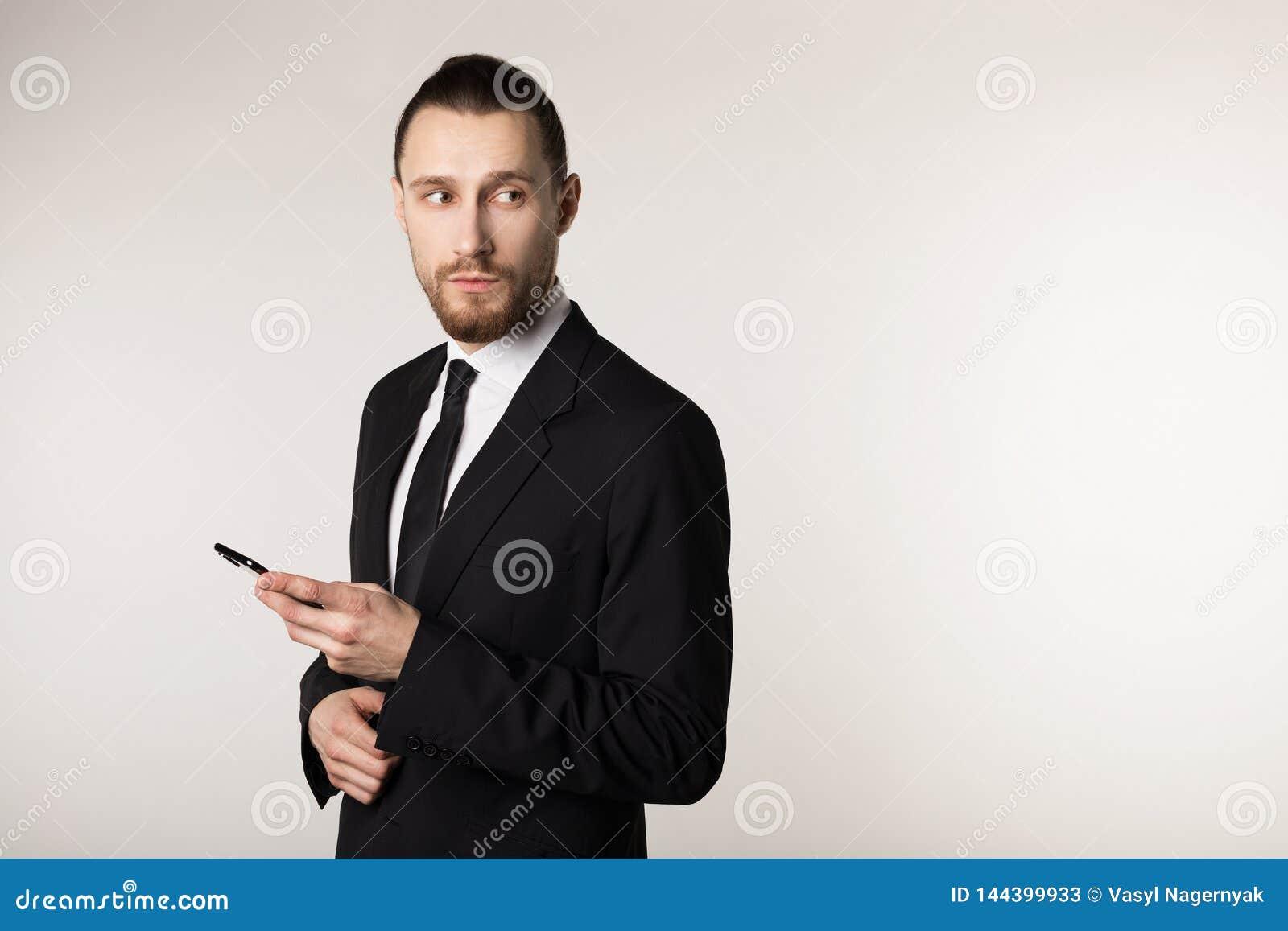 年轻有胡子的人画象的腰部黑衣服身分的与在手中笔,看