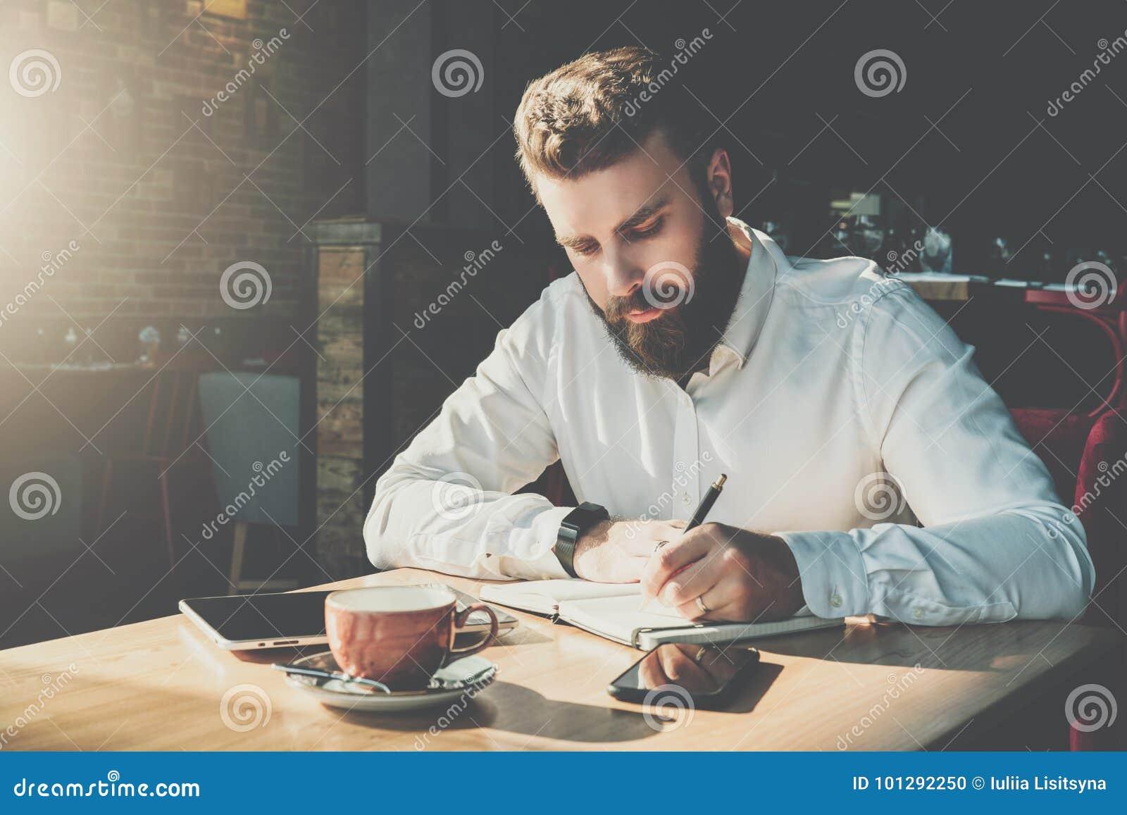 年轻有胡子的商人在咖啡馆在笔记本坐在桌上并且写 在桌片剂计算机上,智能手机 人是