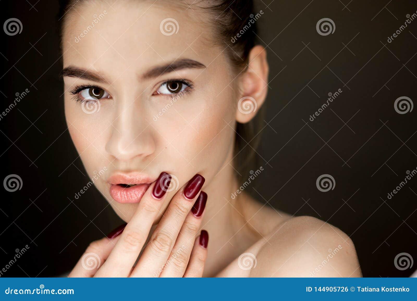 年轻棕色毛发的女孩画象有握她的在她的面孔的自然构成的手指