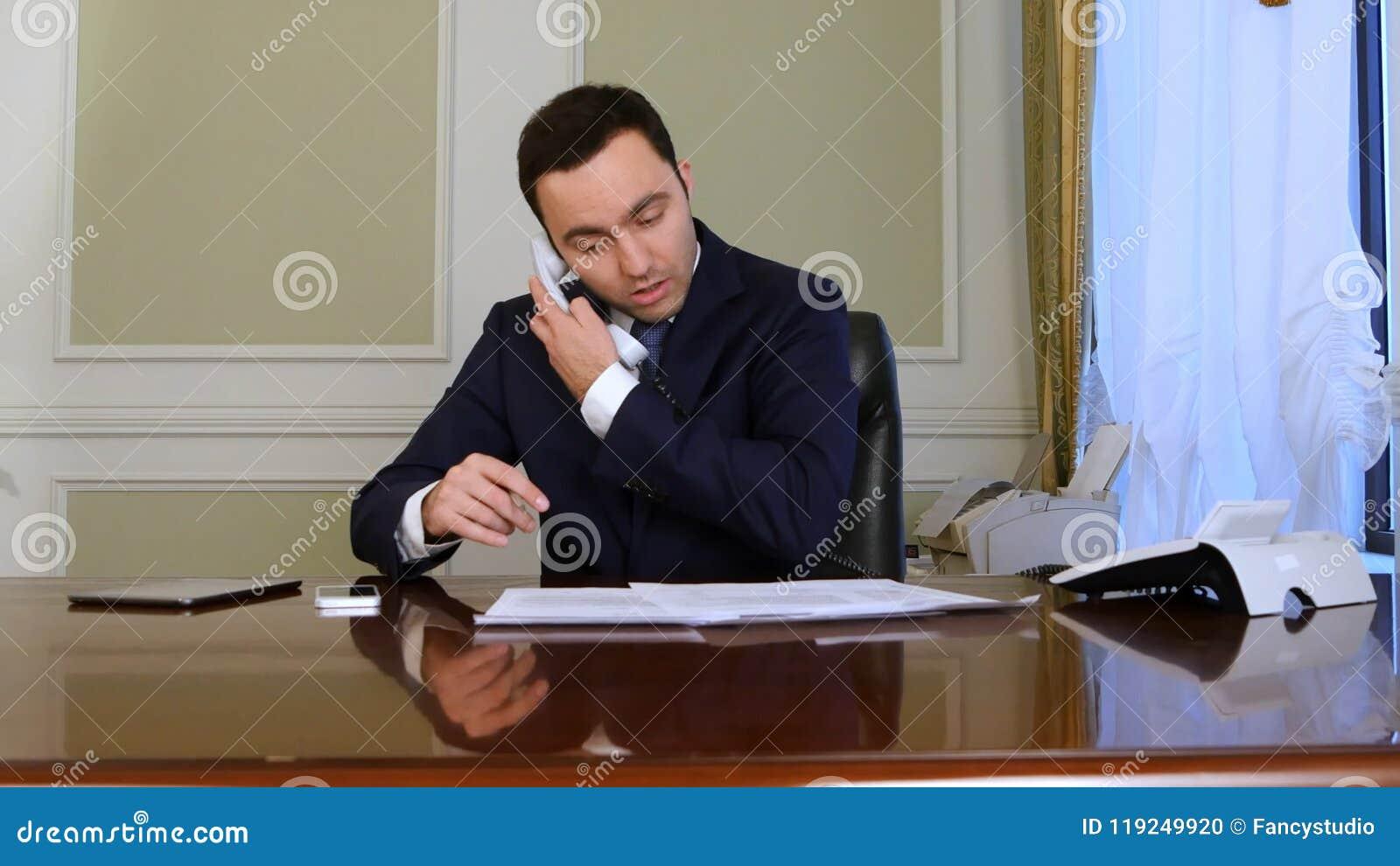年轻残疾商人, saffered从帕金森s疾病,坐在办公室椅子,做文书工作和回答
