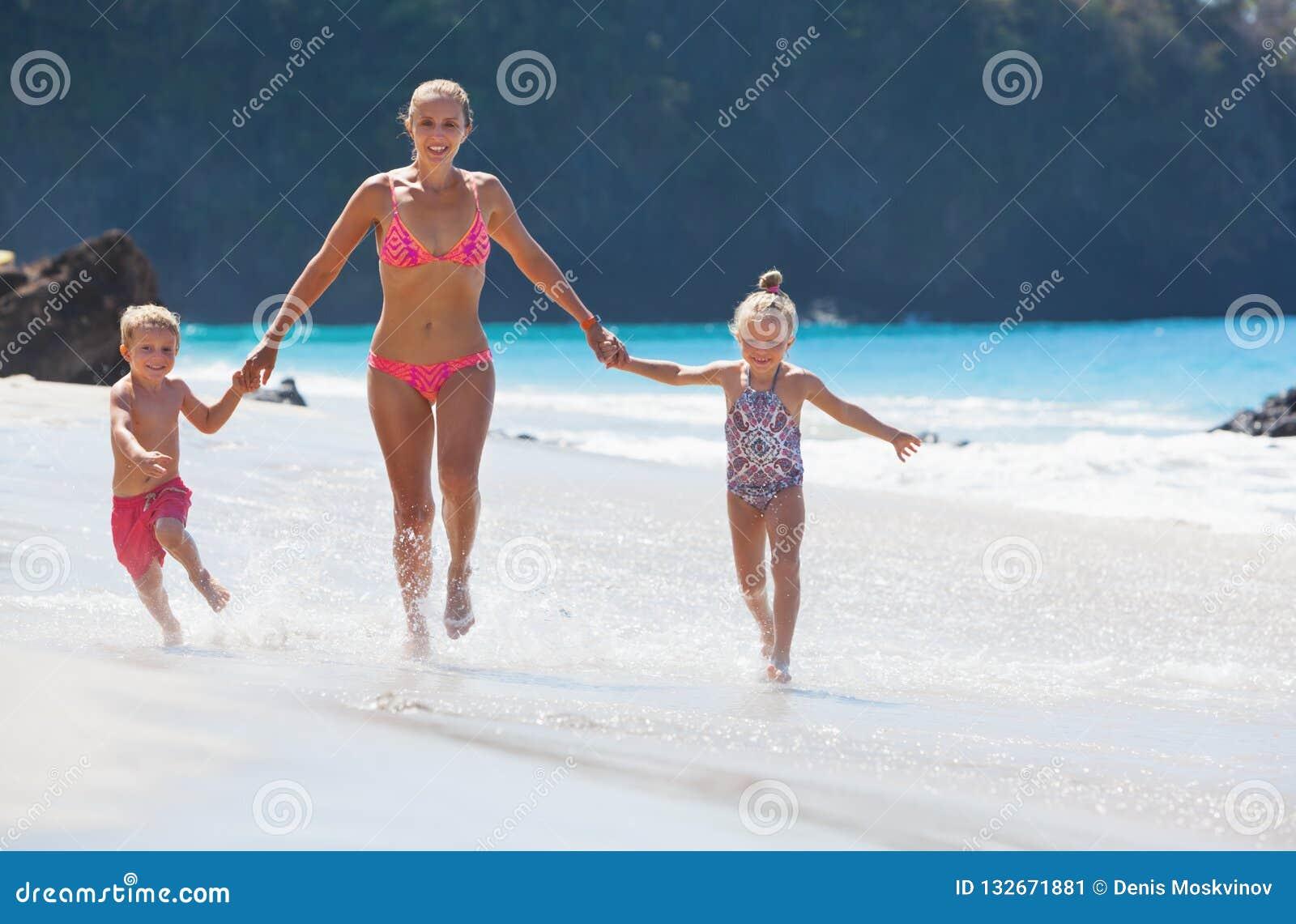年轻母亲,女儿,儿子由沿海的水池负责