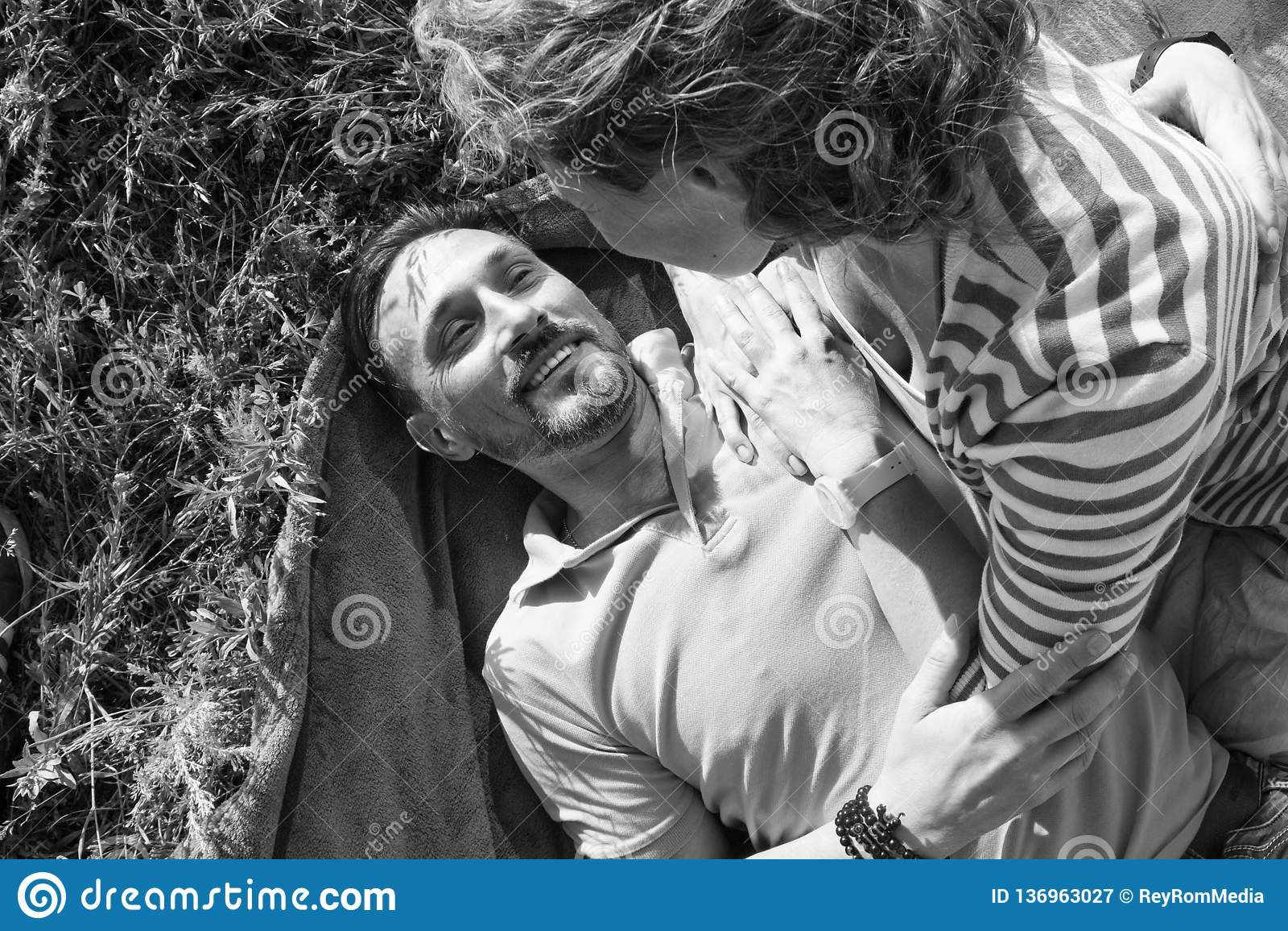年轻浪漫夫妇特写镜头晴天在公园 快乐的男人和妇女拥抱,当有在草甸时的野餐 他们