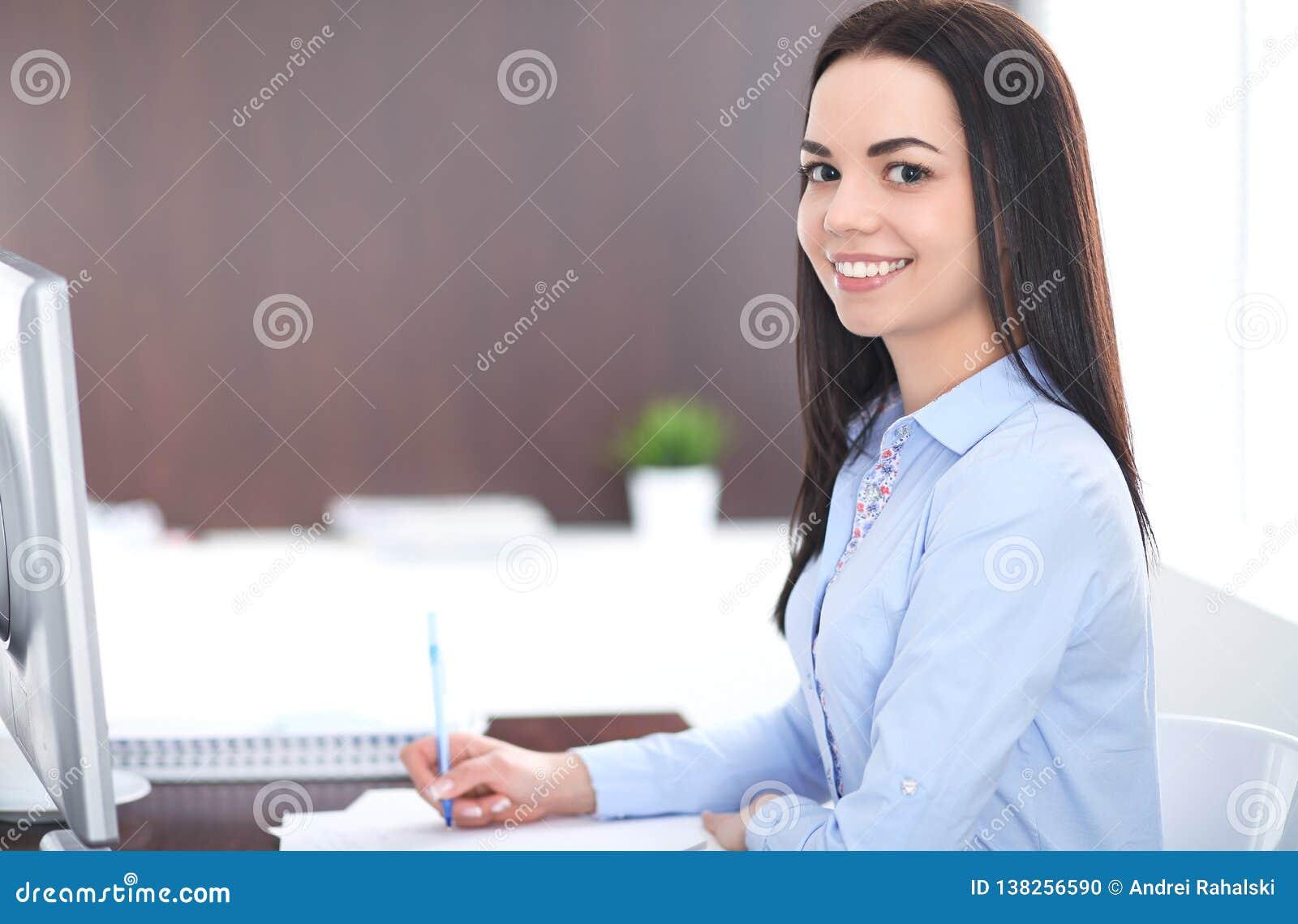 年轻深色的女商人看起来工作在办公室的学生女孩 西班牙或拉丁美洲的女孩愉快在工作