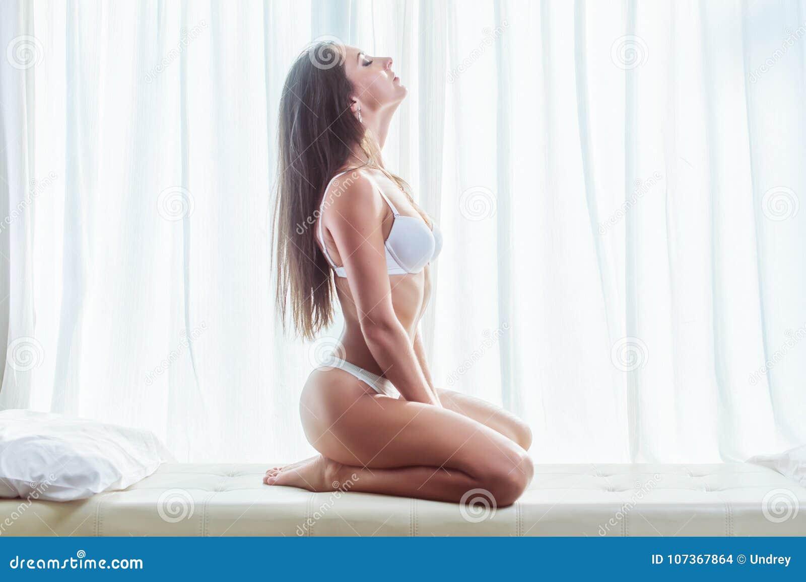 年轻深色的妇女佩带的女用贴身内衣裤侧视图坐与窗口和帷幕的白色床在背景中