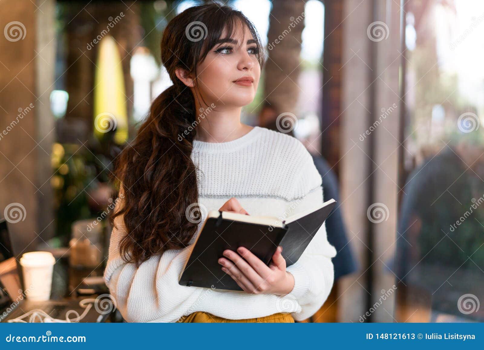 年轻深色的妇女身分画象在咖啡馆的,写在笔记本,看窗口 女孩做在日志的笔记,计划
