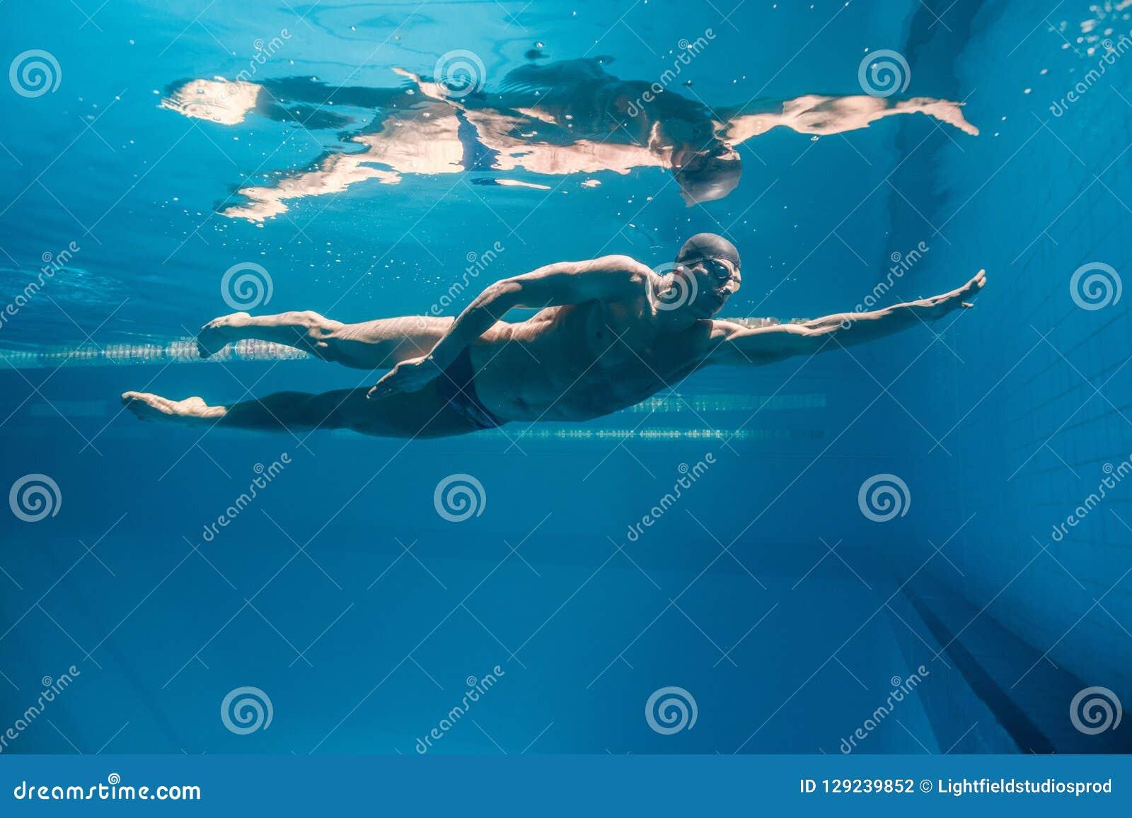 年轻游泳者的水下的图片风镜行使的