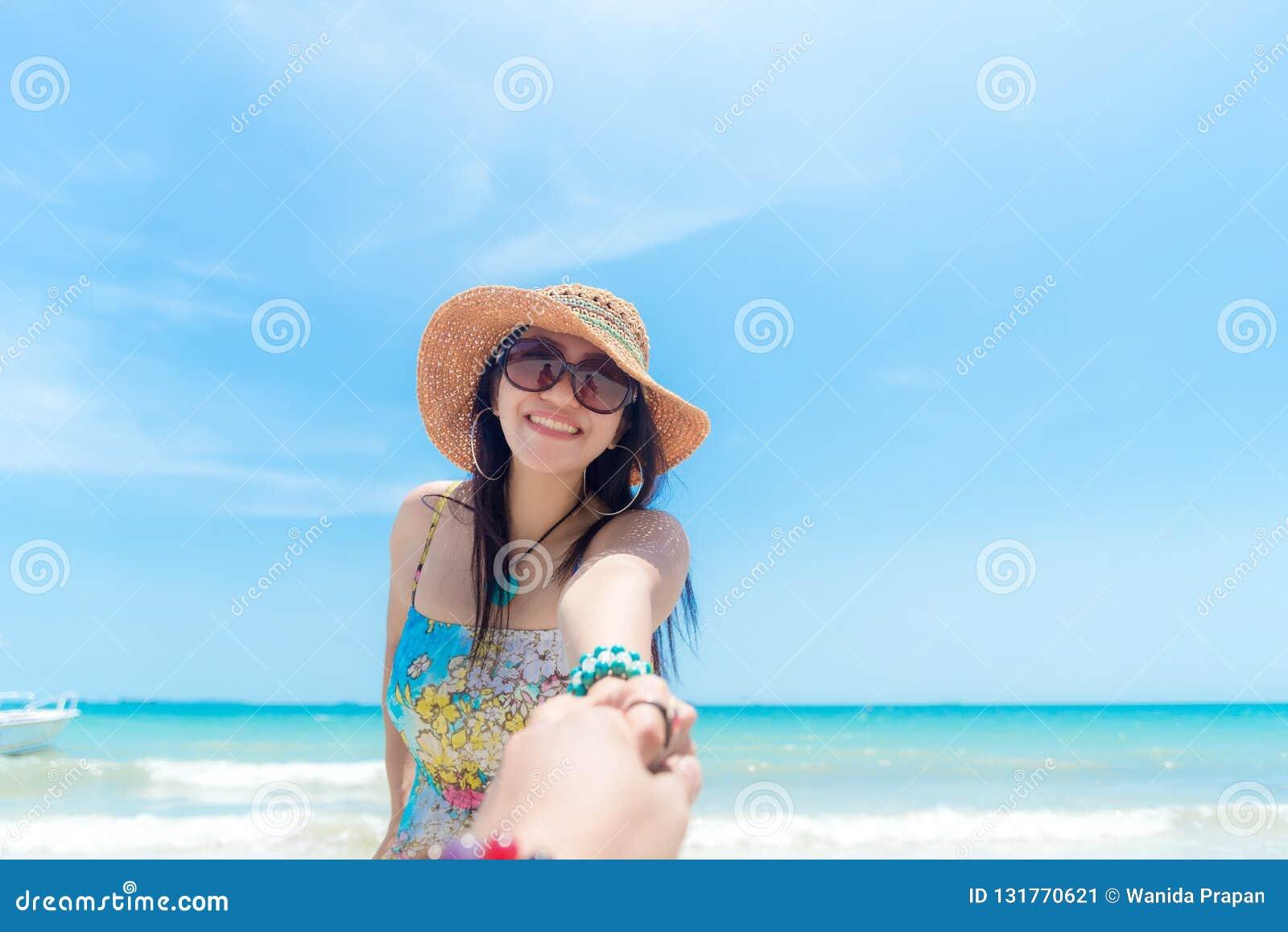 年轻爱夫妇假期浪漫场面在海滩的 手人藏品礼服和帽子走的手妇女