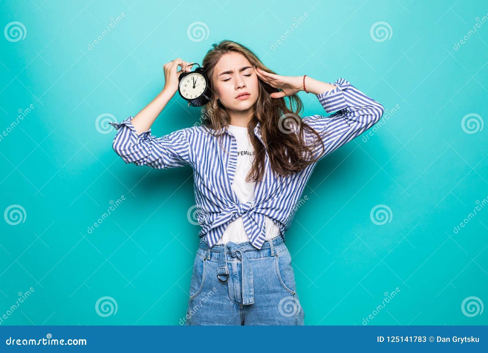 年轻生气困惑的女学生画象牛仔布衣裳的在蓝色背景拿着闹钟被隔绝 运行时间