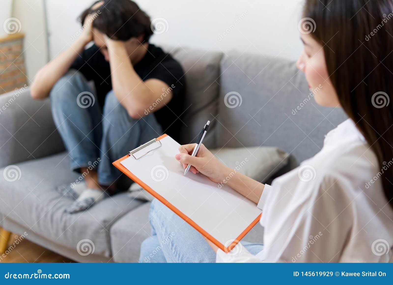 年轻男性患者坐沙发与女性心理学家协商