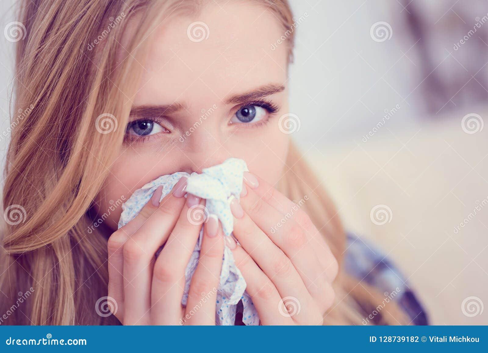 年轻病态的白种人妇女喷嚏在家在有寒冷的沙发 女孩吹她的鼻子的使用的薄纸 医疗和