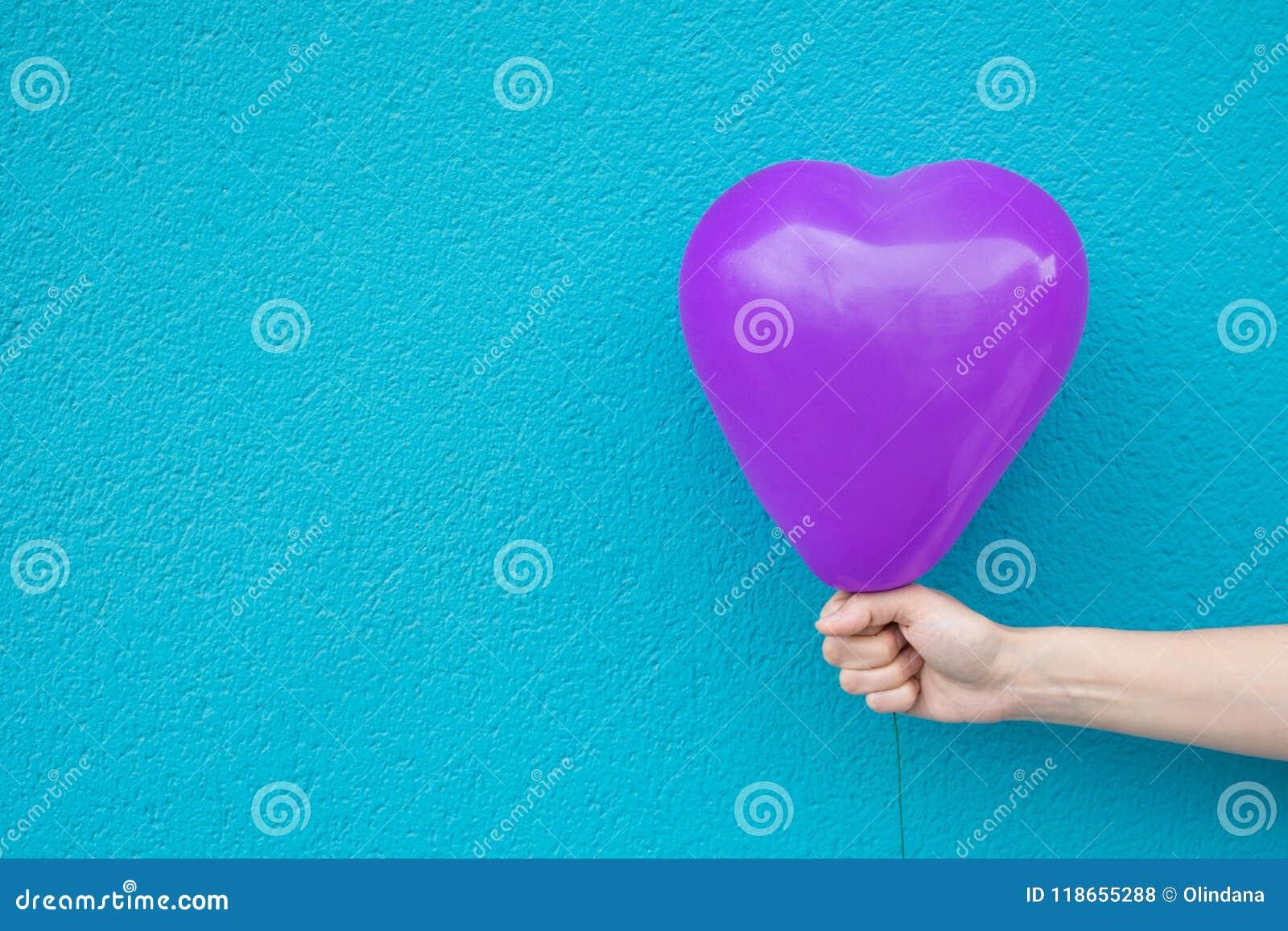 年轻白种人妇女女孩拿着在绿松石被绘的墙壁背景的手中紫色心形的气球 爱慈善