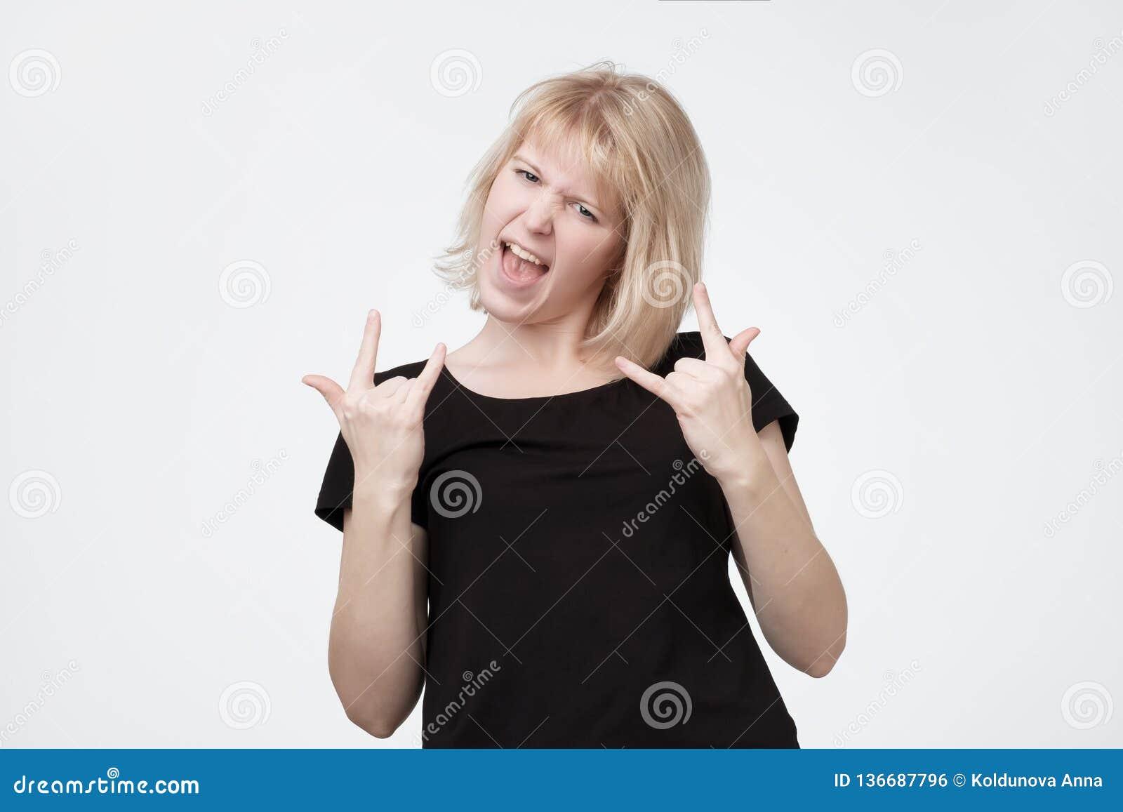 年轻白肤金发的妇女做岩石n卷姿态,听重金属,响亮地惊叹