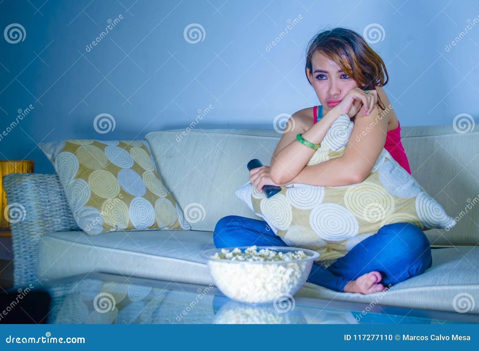 年轻美丽的哀伤的拉丁吃玉米花的妇女观看的戏曲浪漫电影在家坐沙发长沙发夜间在悲伤面孔