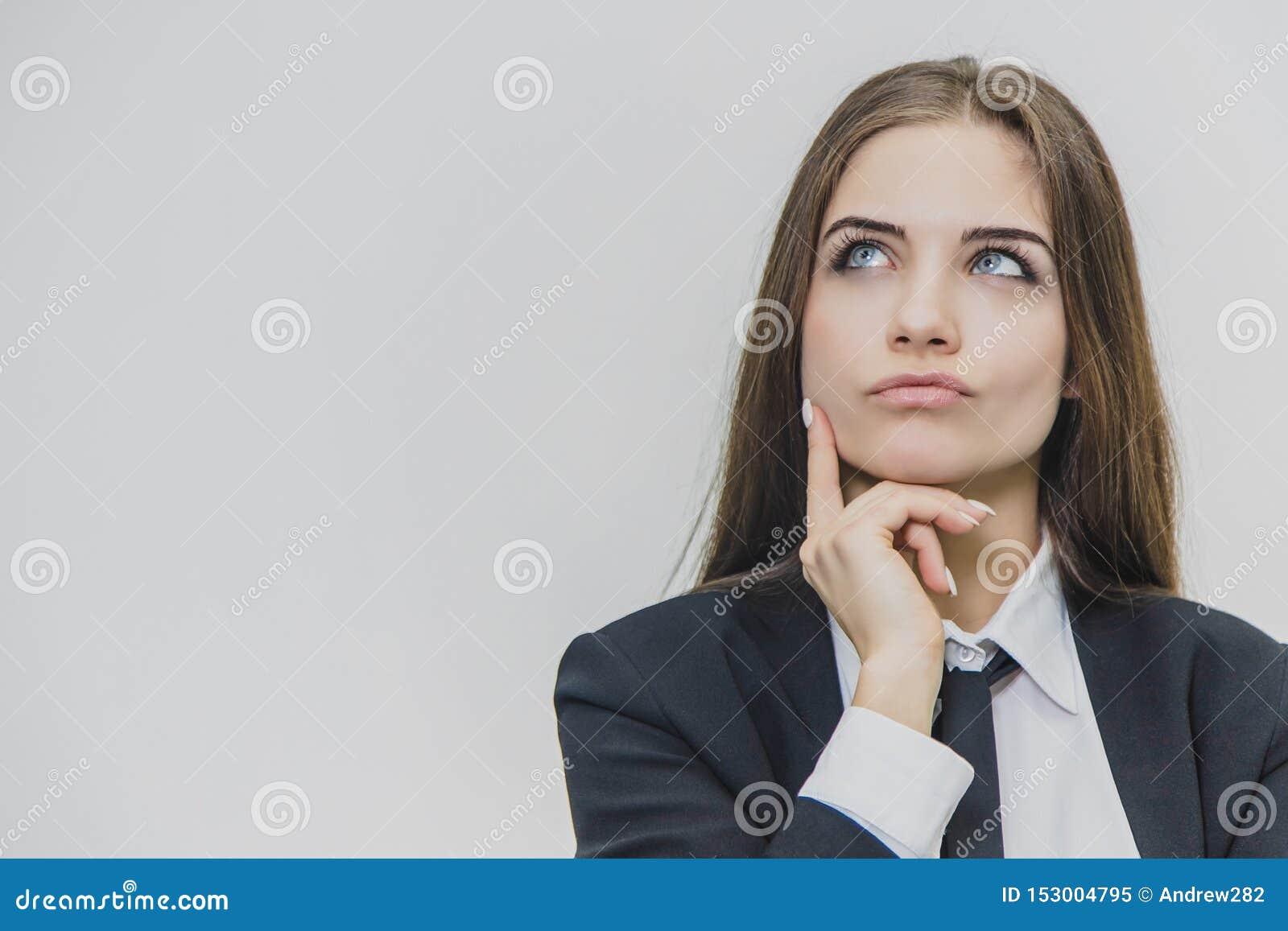 年轻美丽的女实业家是作梦,拿着她的右手在她的下巴附近
