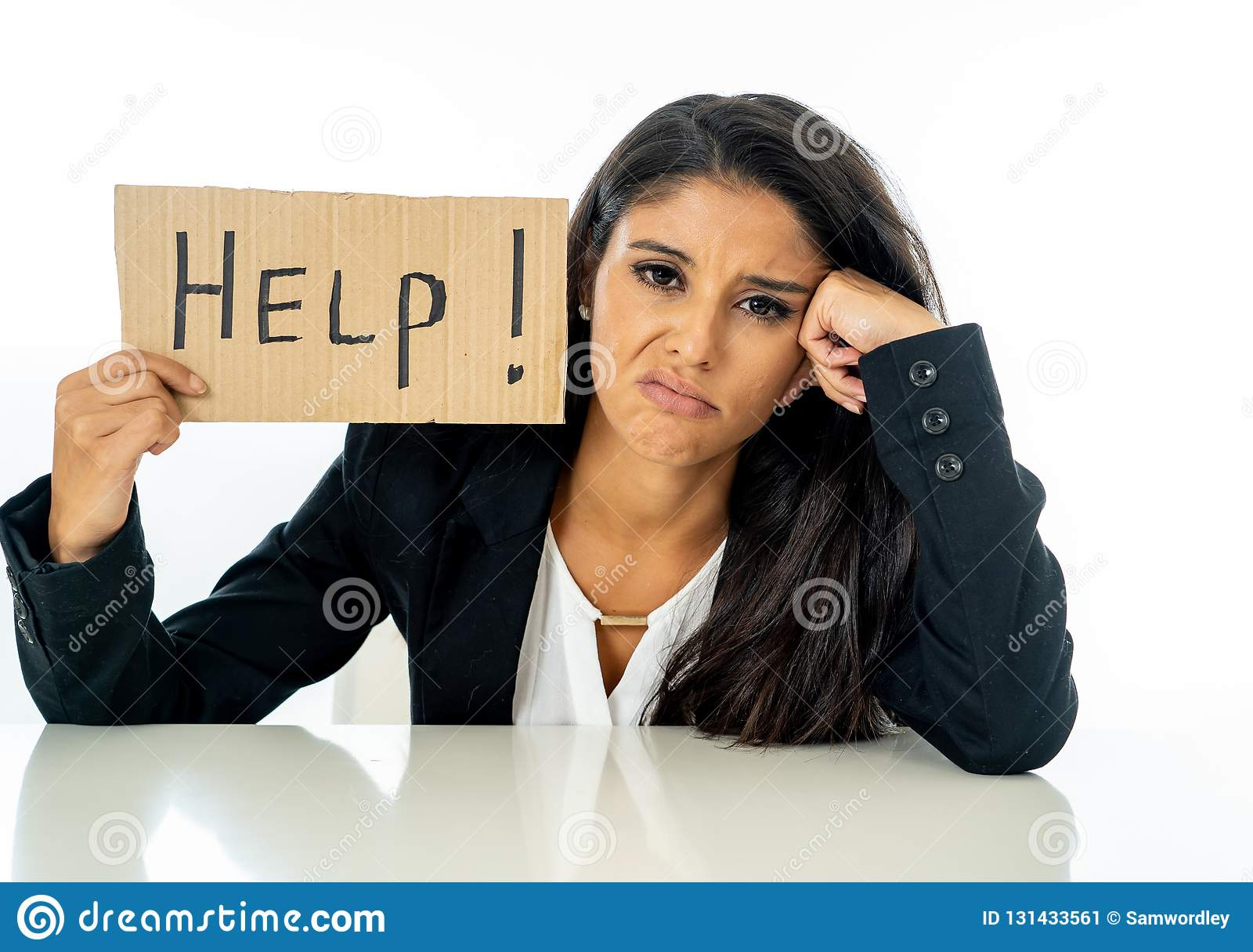 年轻美丽的拉丁女商人被淹没和疲倦拿着帮助标志 看注重,不耐烦,沮丧,生气和