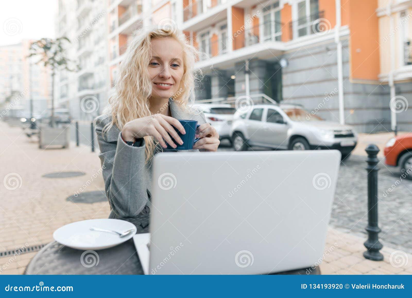 年轻美丽的时兴的白肤金发的妇女画象坐在与手提电脑,水杯的一个室外咖啡馆的衣服暖和的