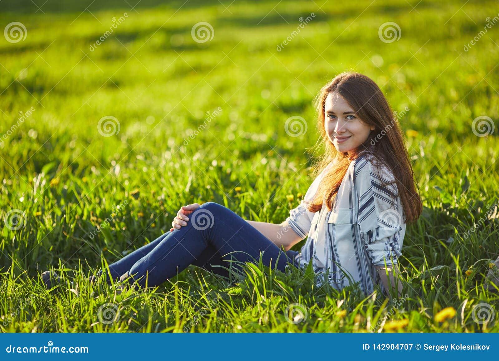 年轻美丽的红头发人妇女坐一个绿色草甸,看照相机