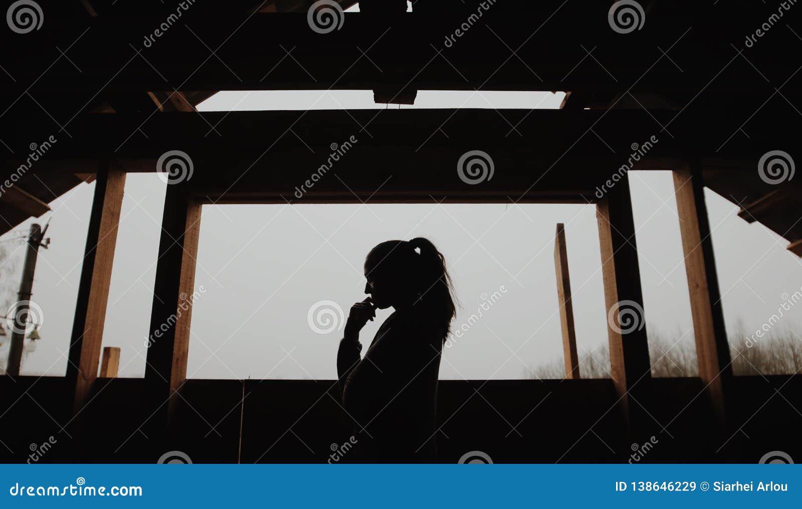 年轻美女剪影在村庄 在一个森林妇女女孩的背景的模型在窗口前面的