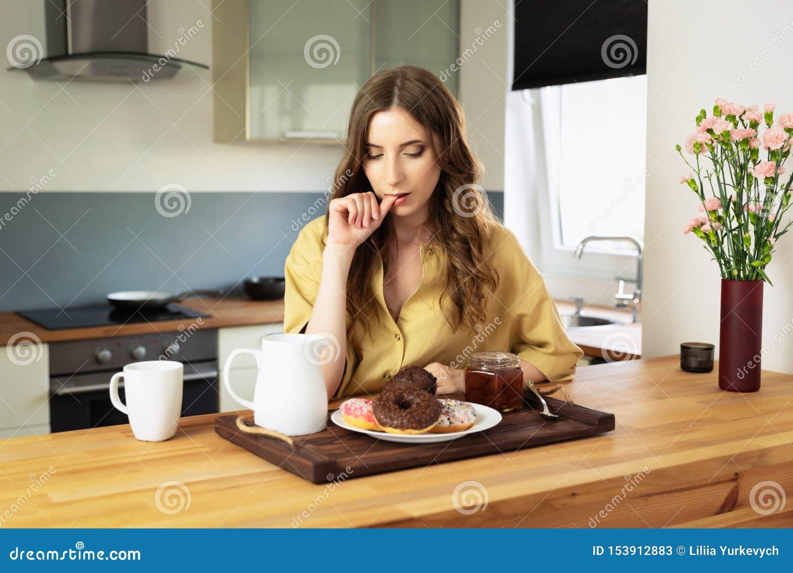 年轻美女食用早餐在家在厨房