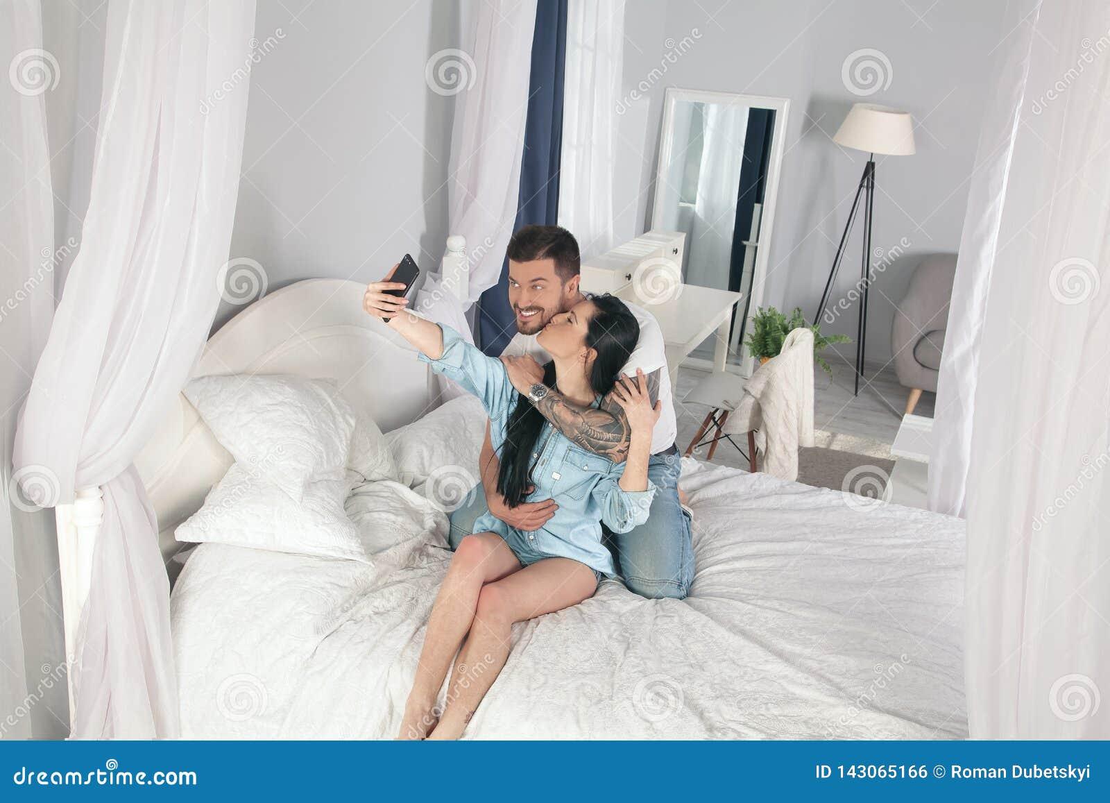 年轻美好和爱恋的夫妇拍在智能手机照相机的selfie照片,当坐在床上在早晨时