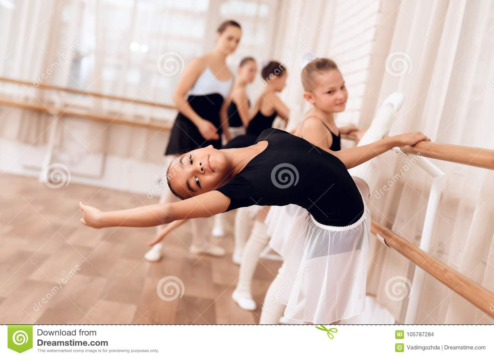 年轻芭蕾舞女演员做舞蹈运动用她的手在类期间在芭蕾学校