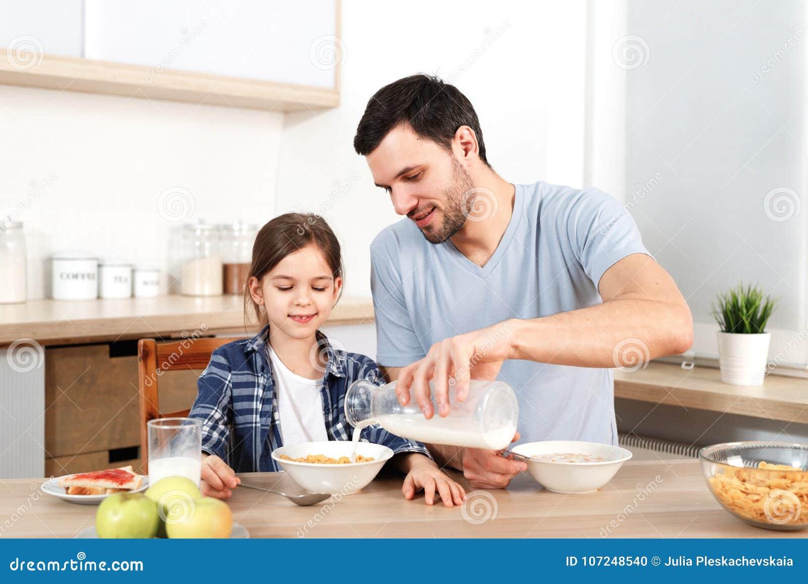 年轻英俊的父亲倒在碗的牛奶有剥落的,早餐为小孩子做准备,在厨房一起坐,有