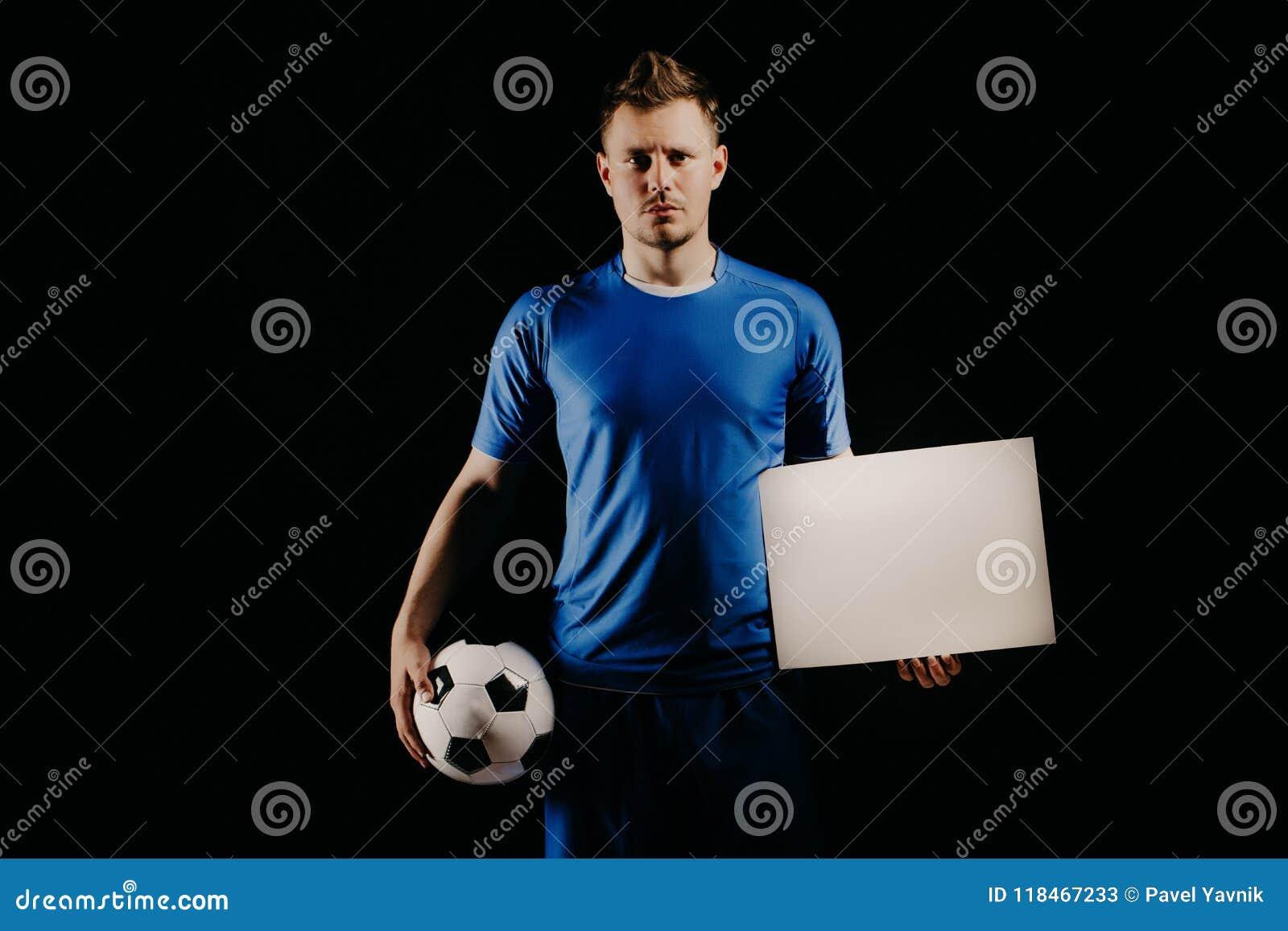 年轻英俊的足球运动员足球拿着球和白色空白在白色