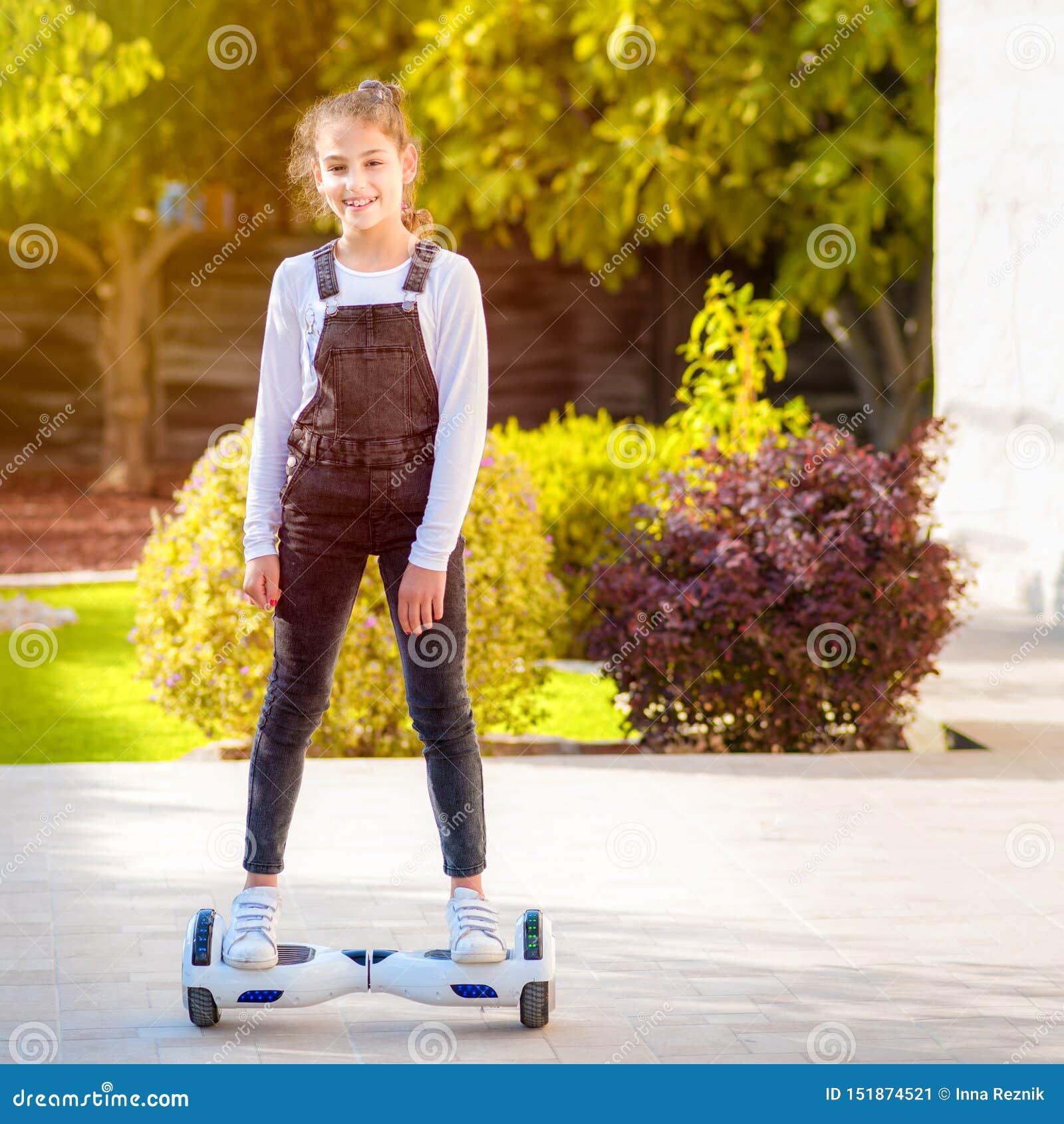 年轻行家少年女孩平衡在电翱翔委员会的,平衡电滑板晴朗的公园的双重轮子自已