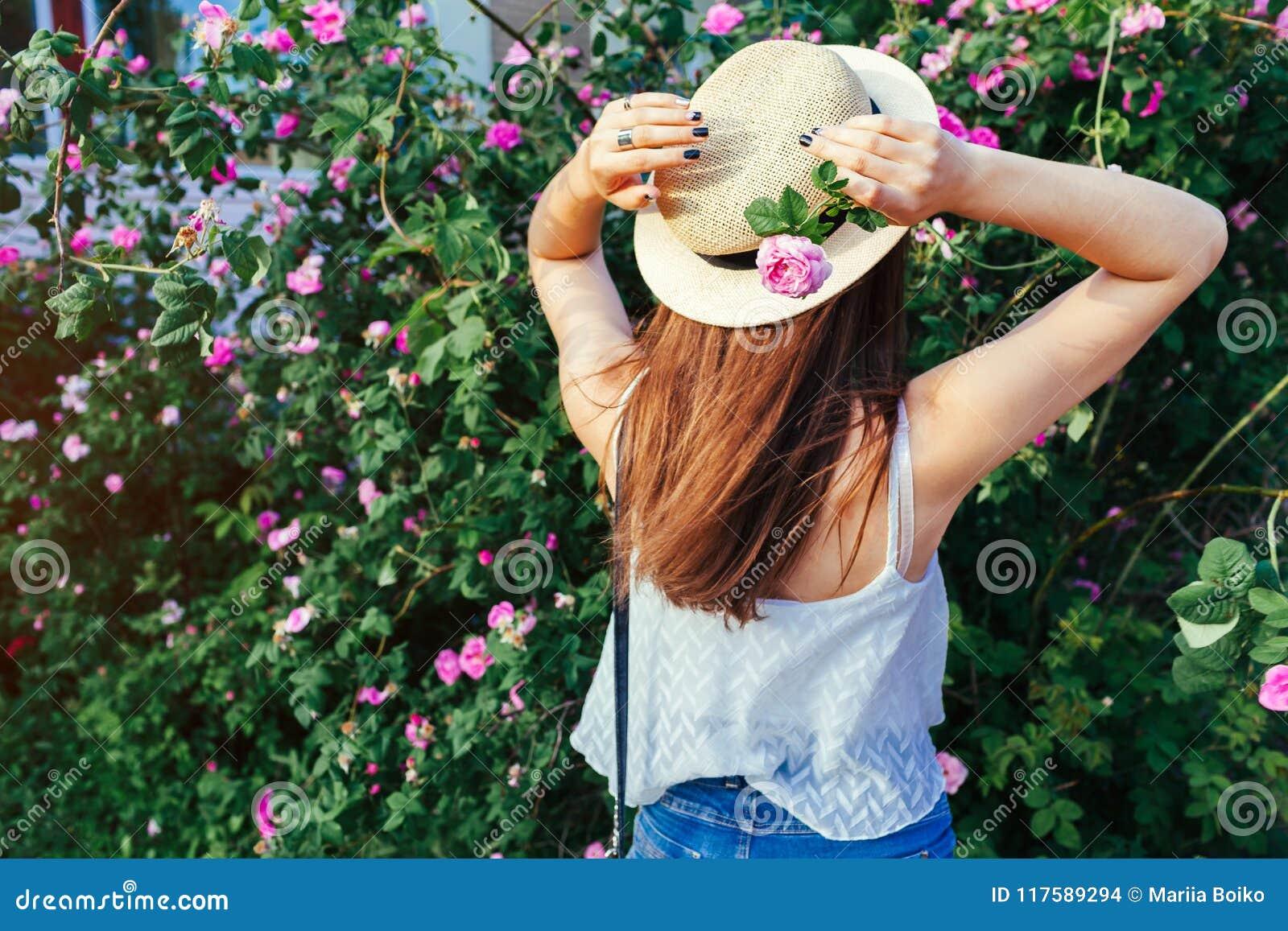 年轻走由开花的玫瑰的行家女孩佩带的帽子 妇女在公园享用花 夏天成套装备