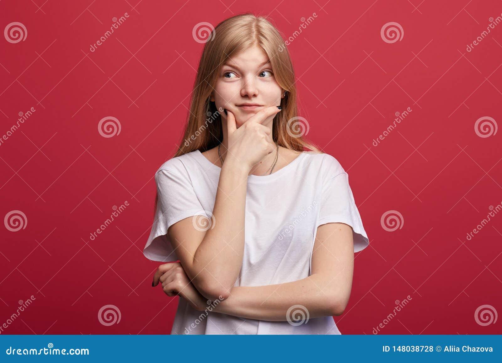 年轻逗人喜爱的妇女用在看她的下巴的手在旁边