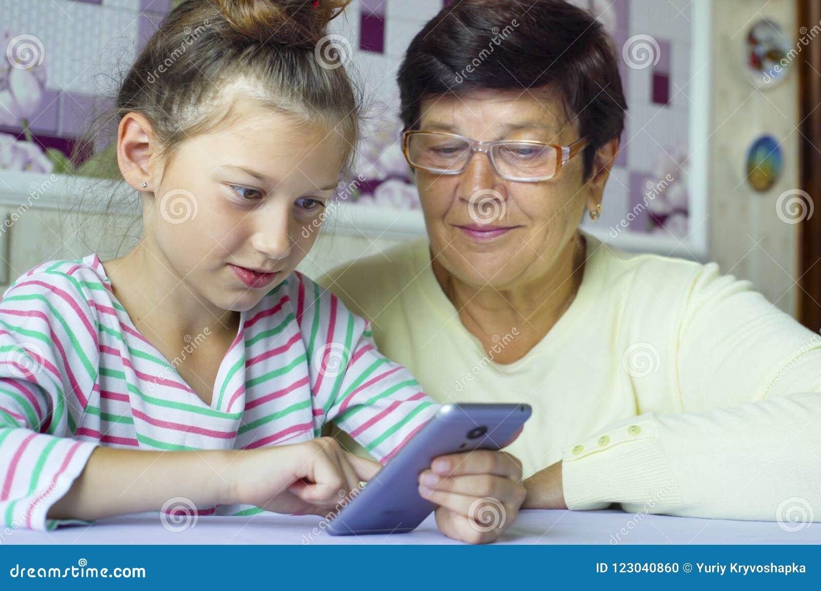 年轻逗人喜爱的孙女教的祖母如何在家使用智能手机