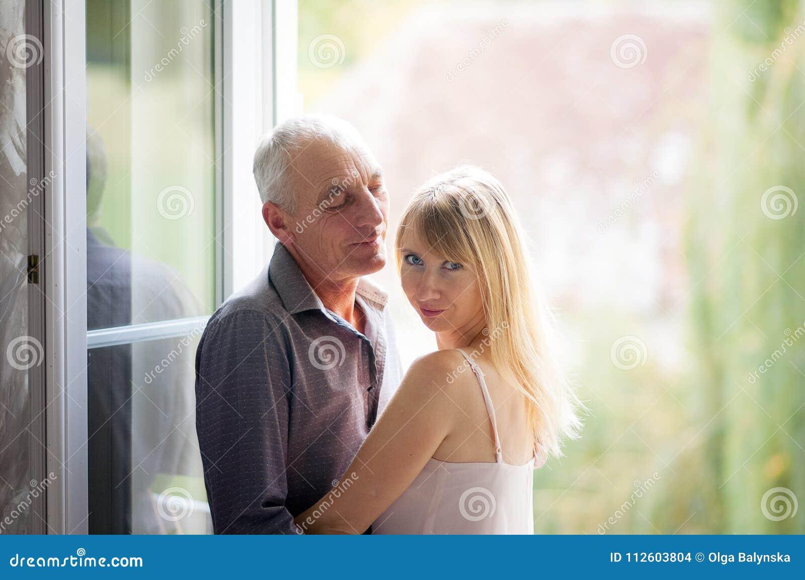 年轻金发的妇女画象站立在与她的资深丈夫的窗口附近的短的夏天礼服的 夫妇