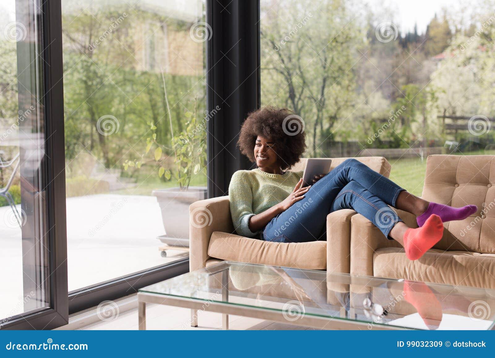 年轻非裔美国人的妇女在家使用数字式片剂