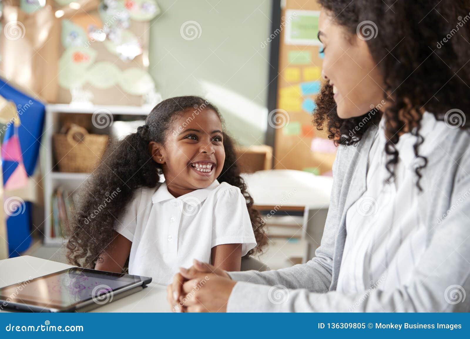 年轻黑人女小学生在与一台片剂计算机的一张桌上在学会一的一间幼儿学校教室坐一个用女性茶