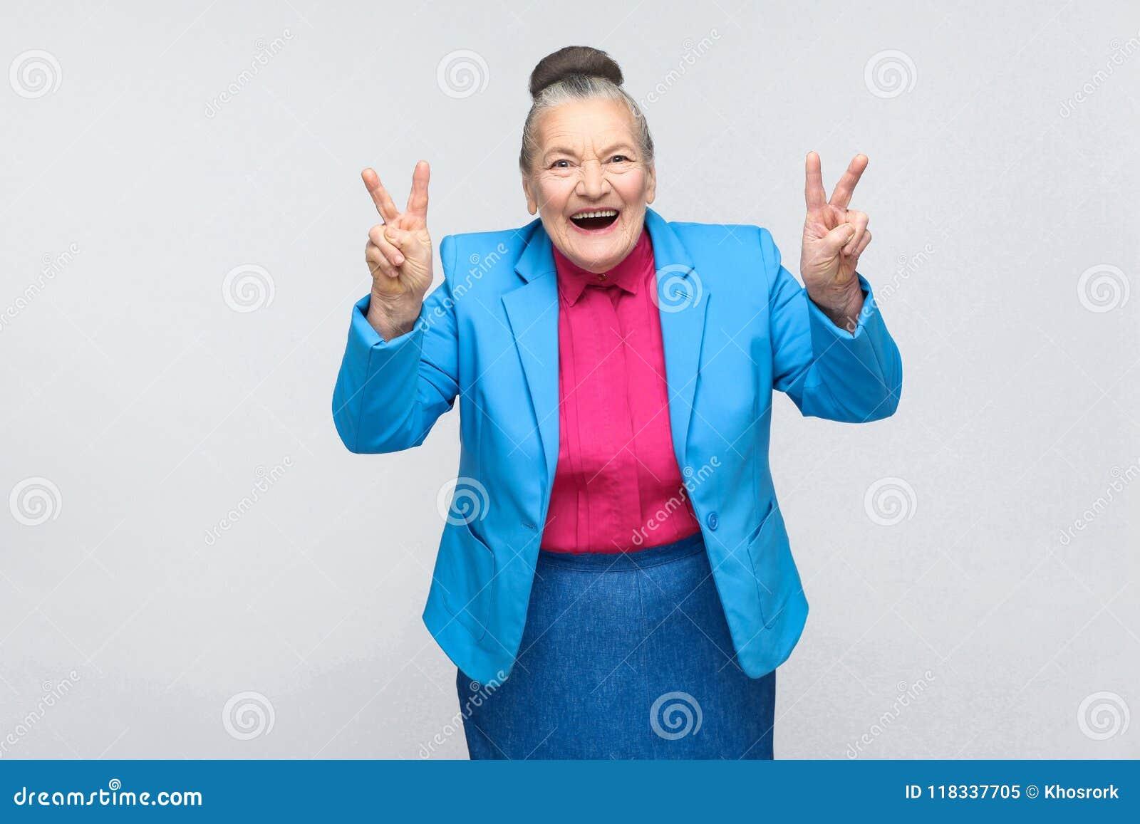 年迈的妇女笑和显示在照相机的和平或胜利标志