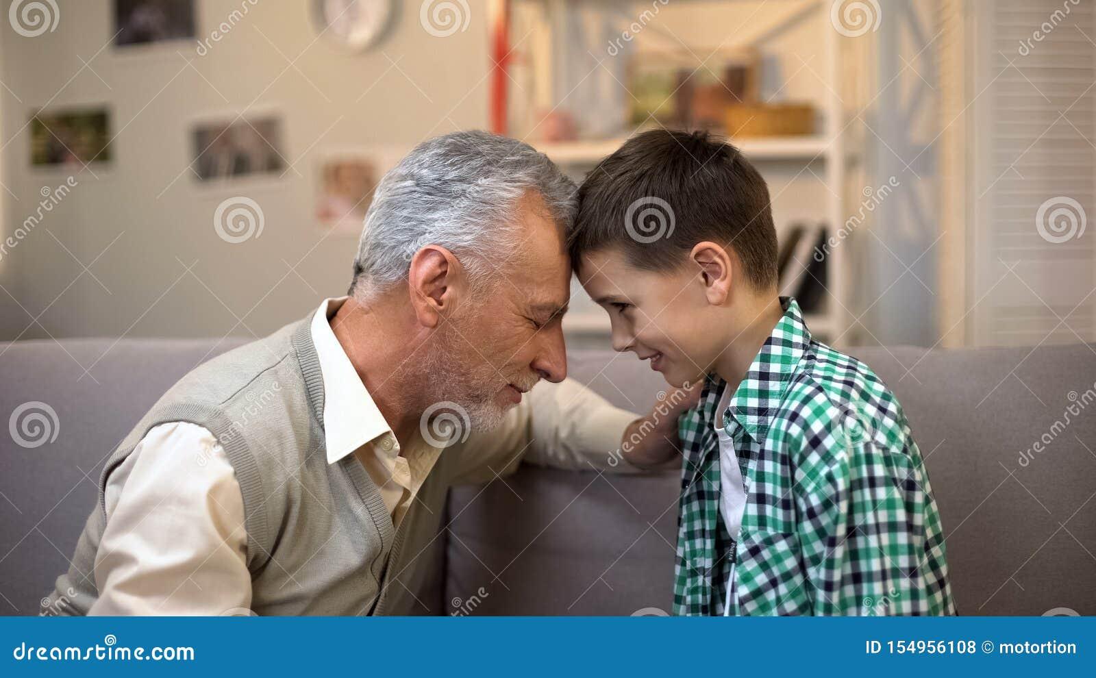 年迈的接触前额、友谊在祖父之间和孙子的男性和男孩